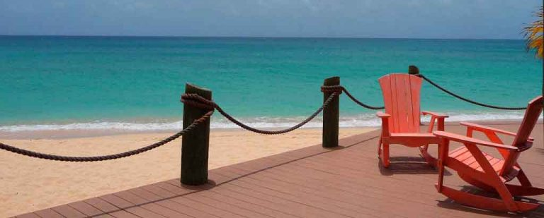 Serene scene of 2 empty rocking chairs on a wooden deck a few steps away from turquoise Caribbean waters